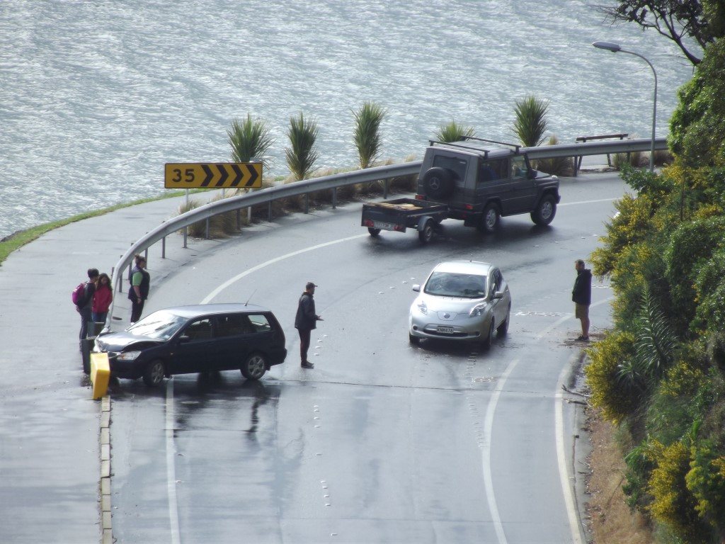 Bystanders assist after a single vehicle accident at Burns Point yesterday afternoon. Photo David...