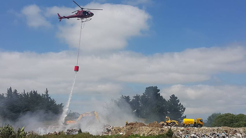 A helicopter with a monsoon bucket helps fight the blaze. Photo: George Block