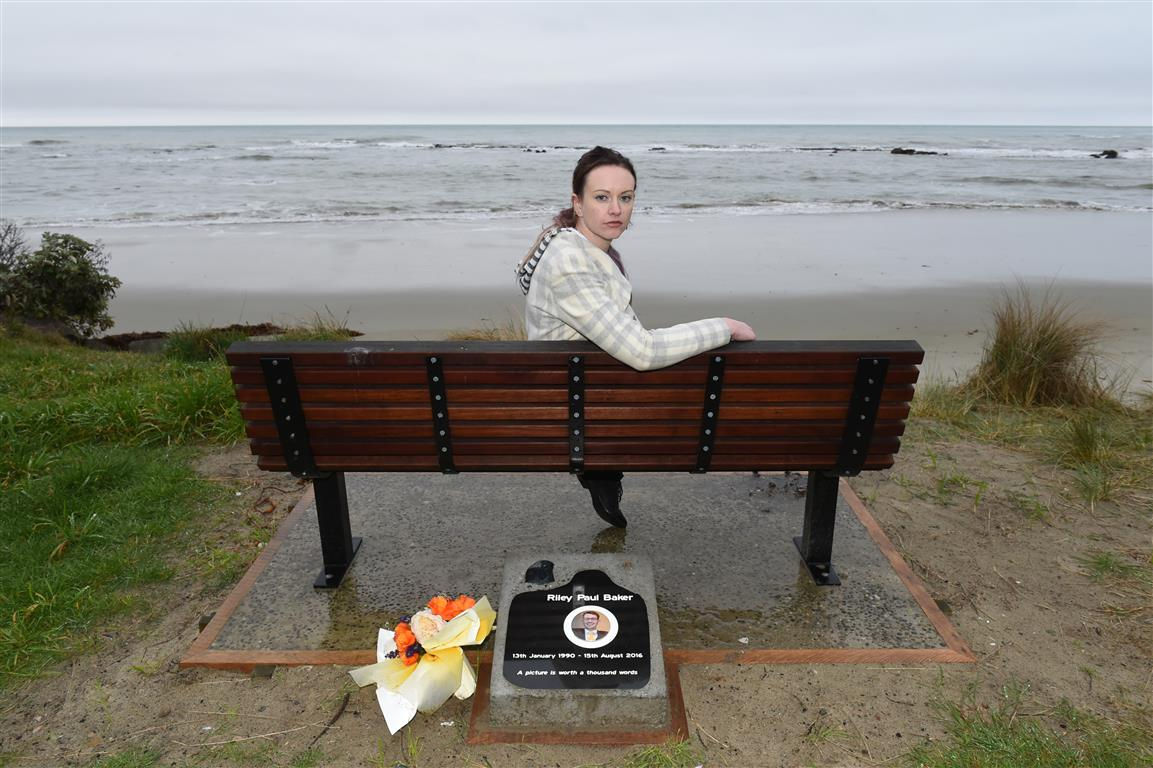 Sarah Baker sits on the memorial seat for her brother, Riley, near Shag Point. Photo: Gregor...