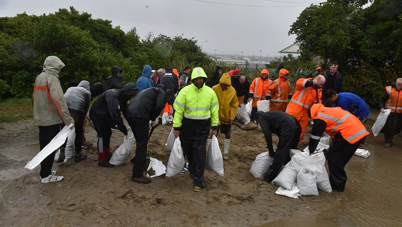 Volunteers help fill sandbags at the St Clair Tennis Club  in Victoria Rd. Photos Gregor...