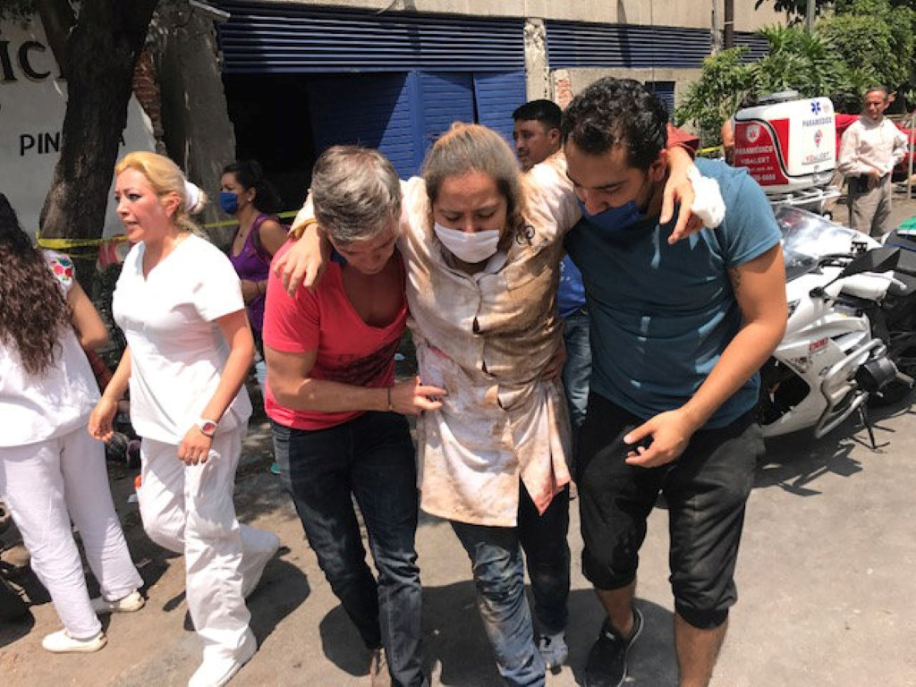 People assist an injured woman after the quake hit in Mexico City. Photo Reuters