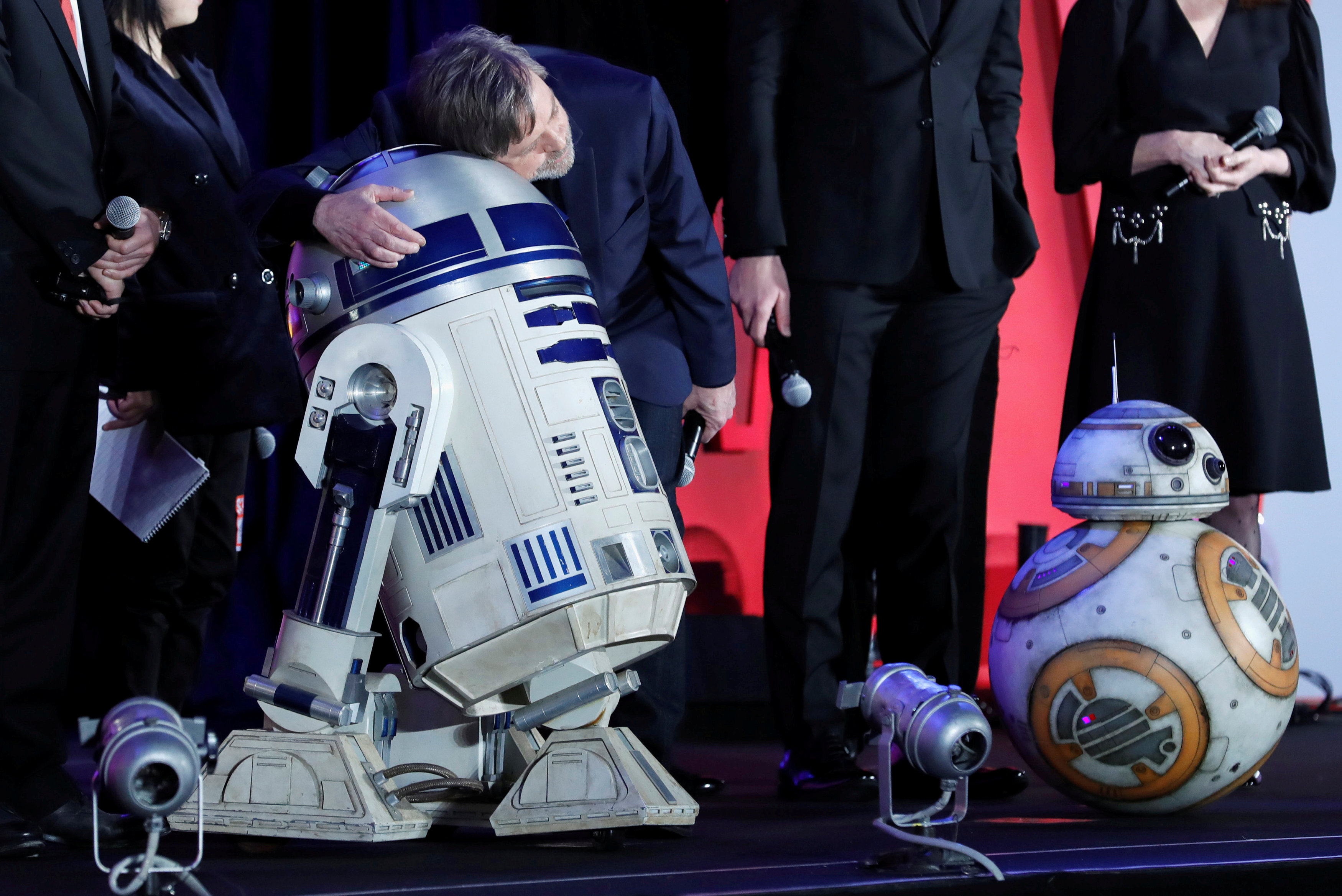 Mark Hamill, who plays Luke Skywalker in the Star Wars, series hugs R2D2 at an event promoting...