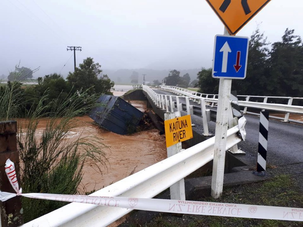 Debris is carried down a river in the small community of Bainham in Golden Bay. Photo: Reuters