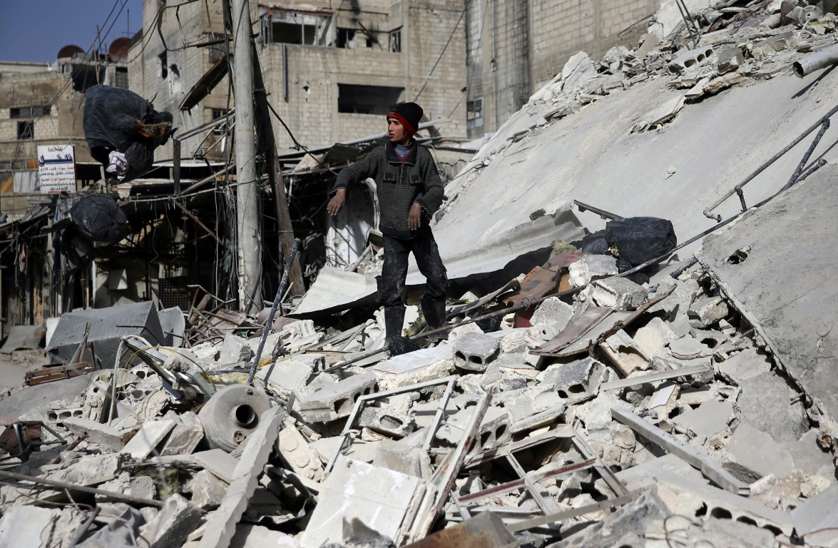 A boy stands on the rubble of a damaged building in the besieged town of Douma, Eastern Ghouta....