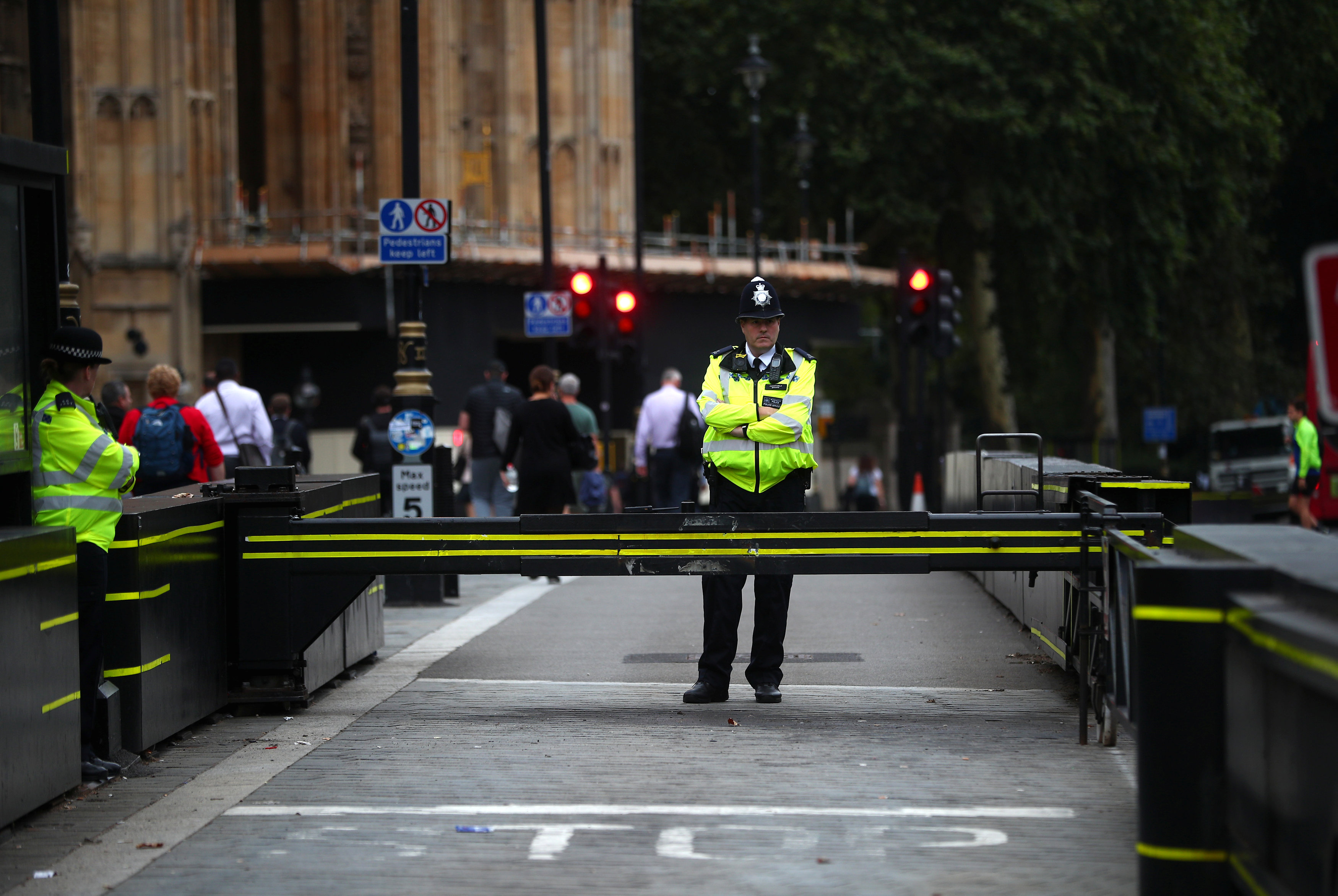 Officers stand at the vehicle barrier to the Houses of Parliament where the car crashed. Photo:...