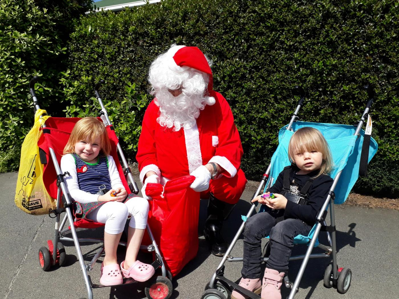 Santa gives out presents to young fans at last year's Green Island Market Day. PHOTO: SUPPLIED
