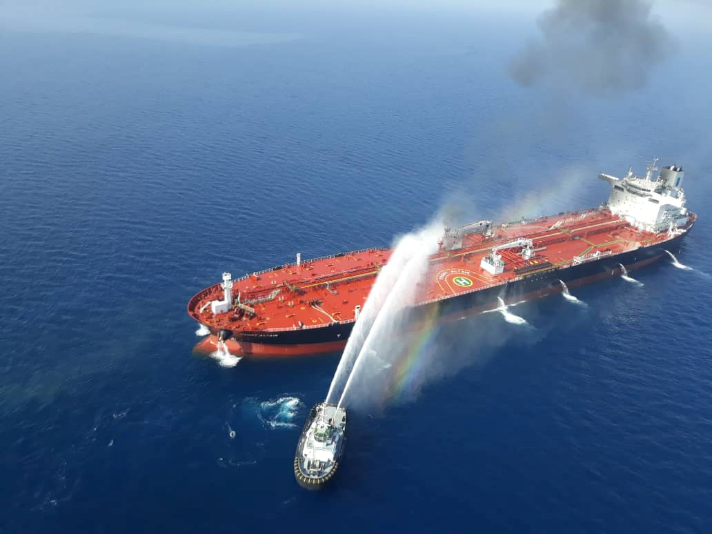 An Iranian navy boat tries to stop the fire on one of the tankers after it was attacked in the...