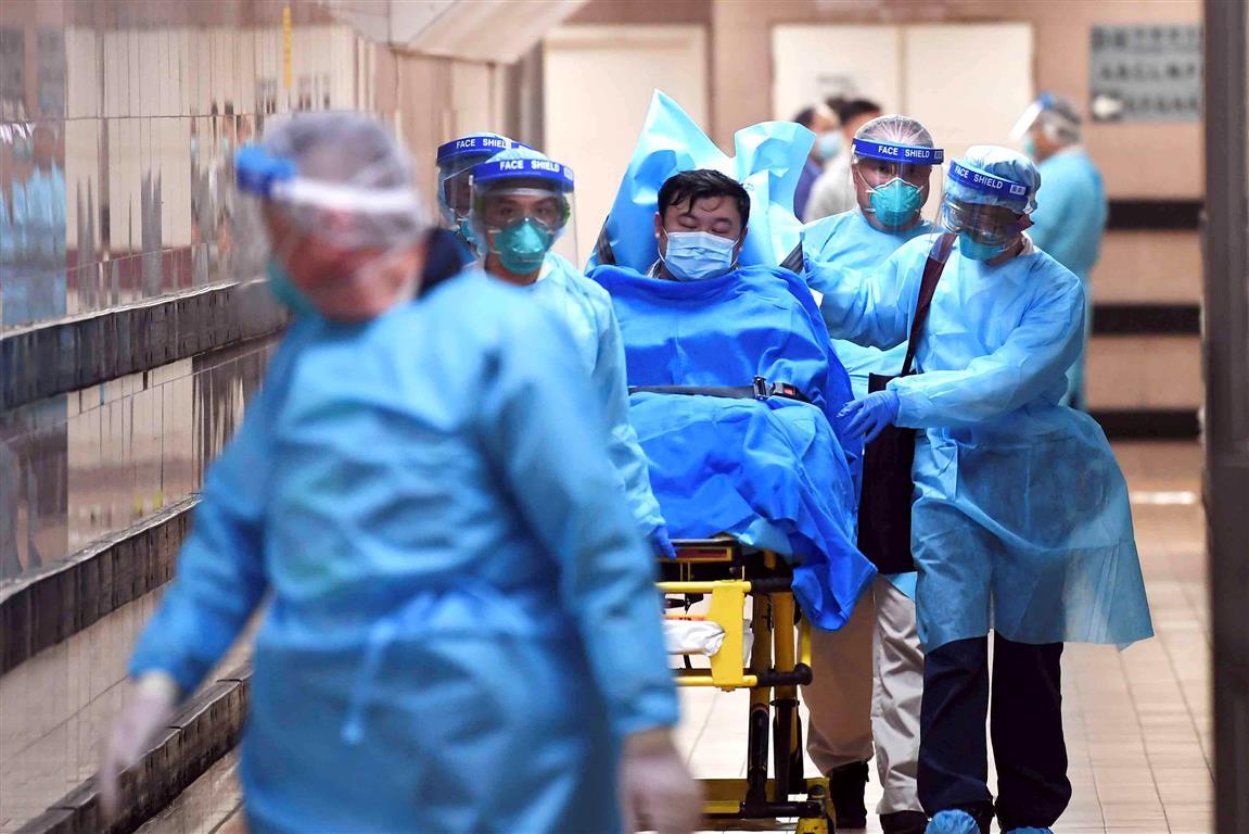 Medical staff transfer a suspected coronavirus patient at Queen Elizabeth Hospital in Hong Kong....