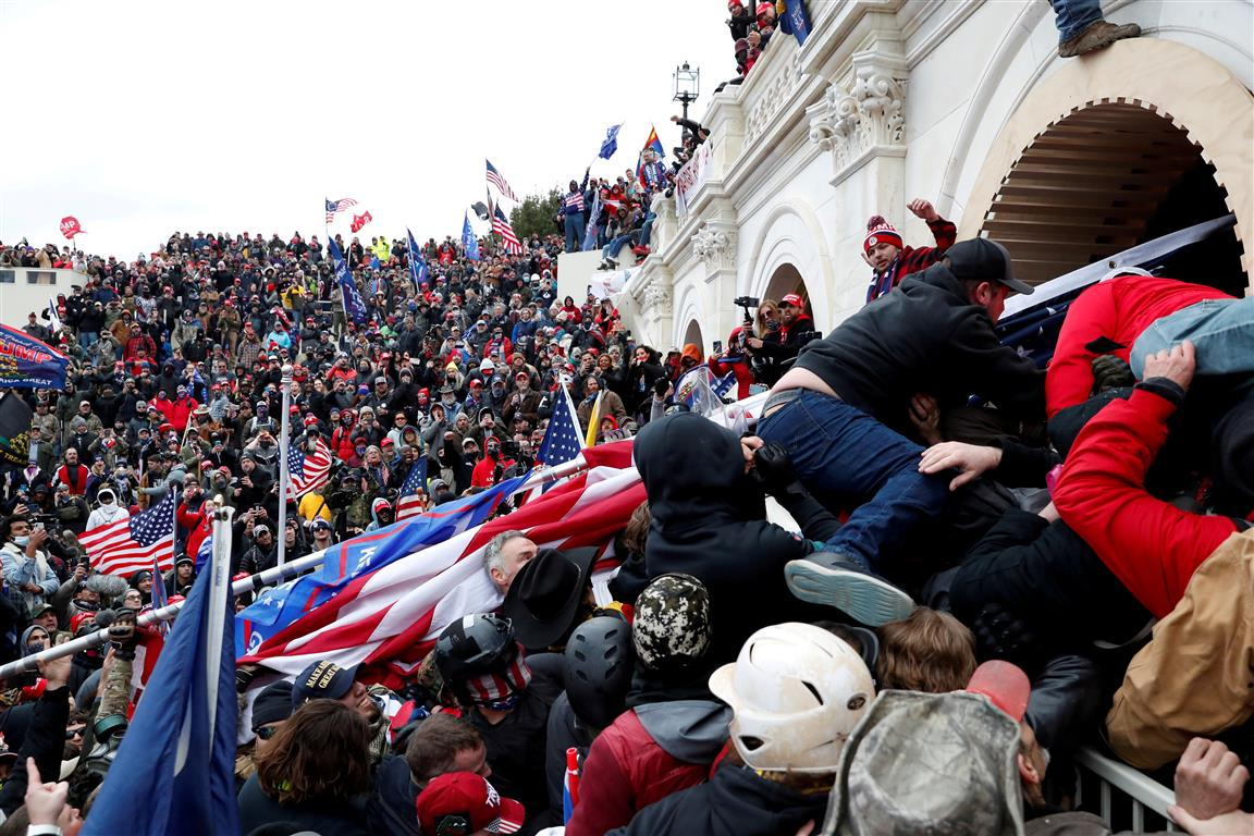 Protesters storm into the US Capitol during clashes with police in Washington yesterday. Photo:...