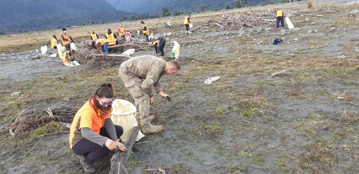 People clean up rubbish spilled from the Fox Glacier landfill. Photo: Photo: supplied
