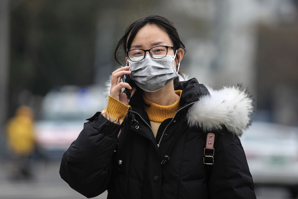 A woman wears a mask while walking past the closed Huanan Seafood Wholesale Market, which has...