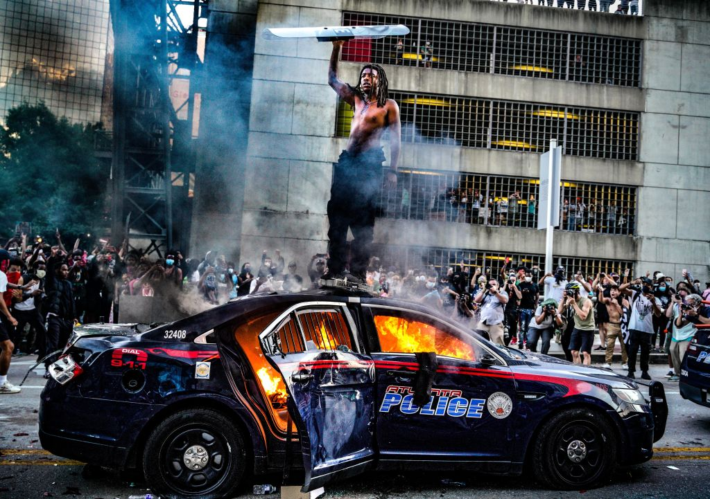 A police vehicle burns outside the CNN Center in downtown Atlanta after being set alight during a...