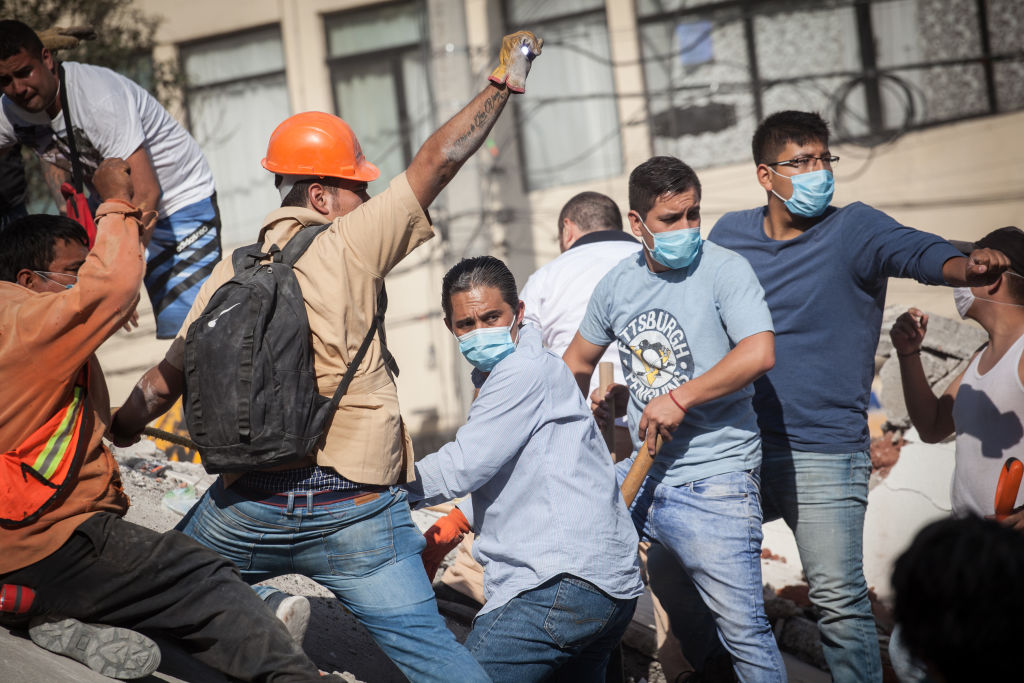 Rescuers look for victims amid the ruins of a building knocked down by the earthquake in Mexico...