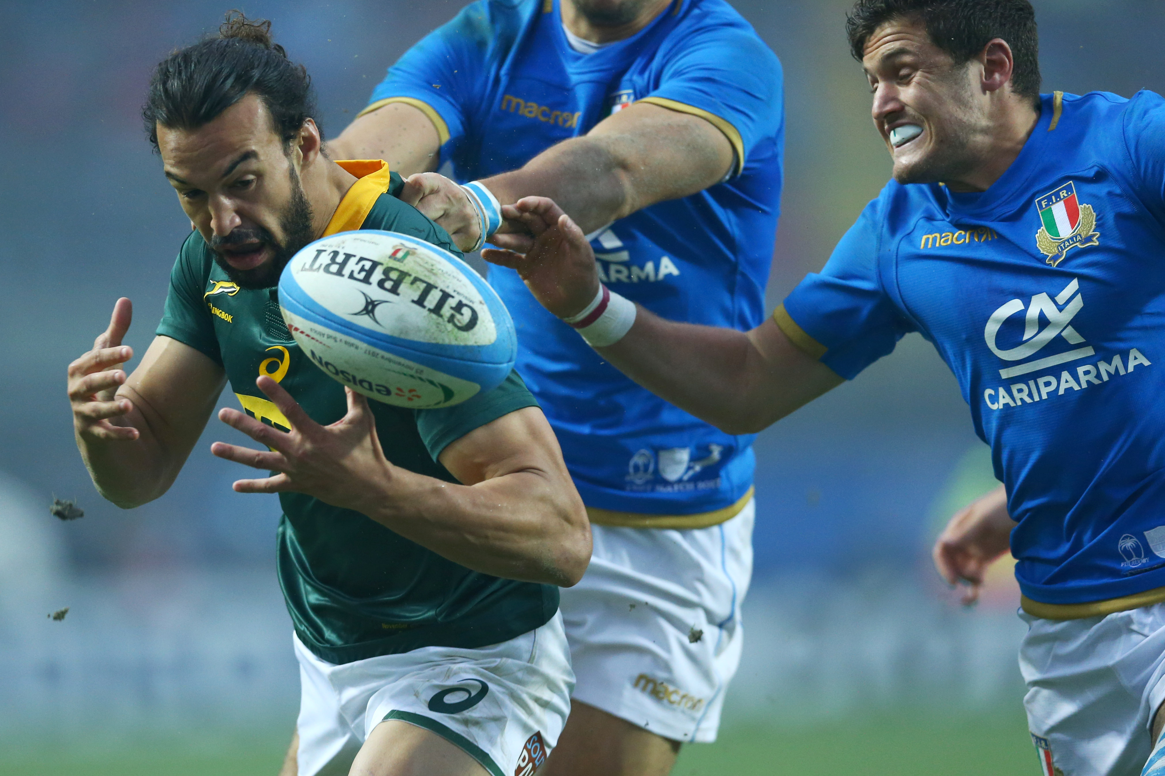 Springbok Dillyn Leyds tries to evade a tackle from Italy's Marcello Violi (right). Photo: Getty Images