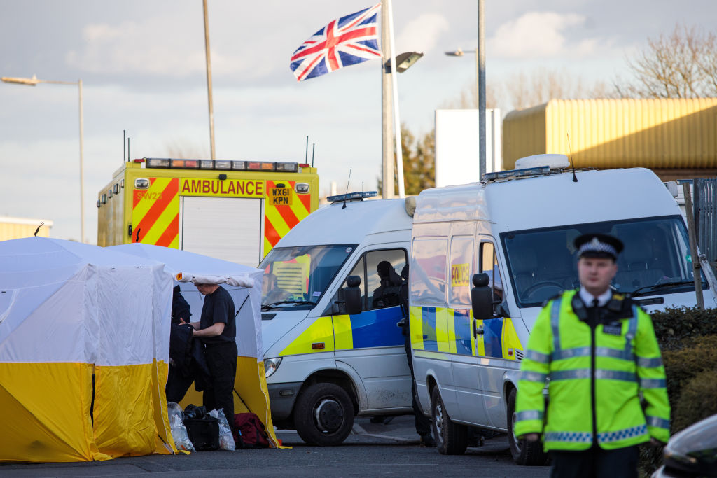 Police officers put on protective clothing in a tent outside a vehicle recovery centre in...