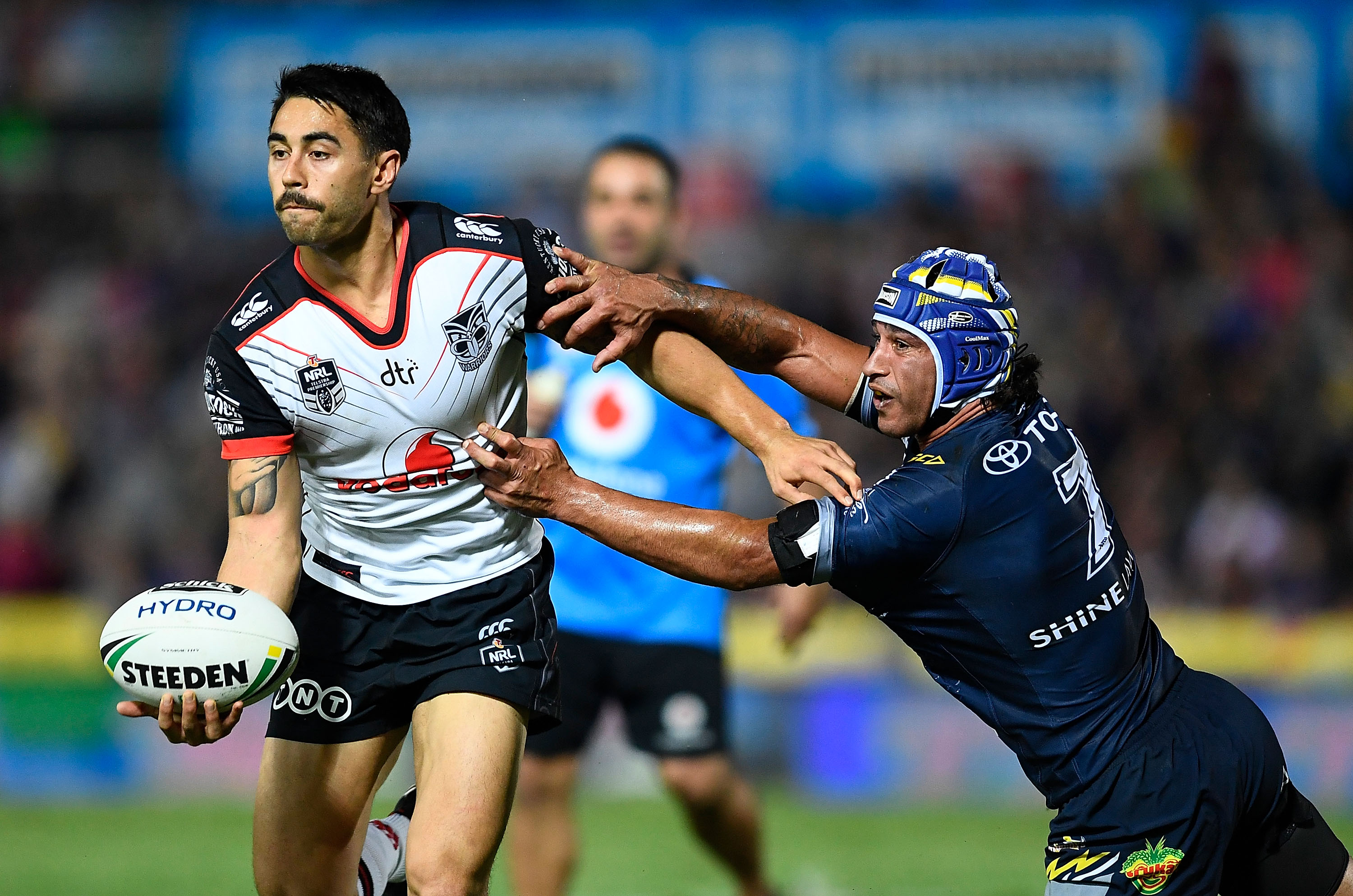 Shaun Johnson, of the New Zealand Warriors, looks to get a pass away despite the tackle of...