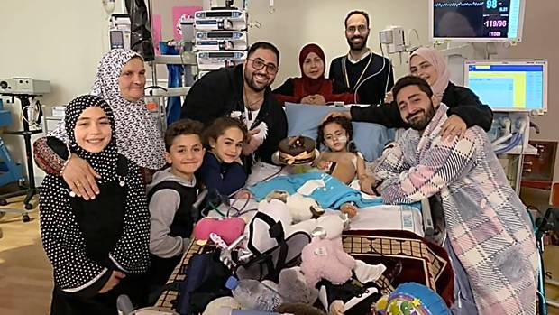 Mosque shooting survivor Alen Alsati is surrounded by family and friends in Starship hospital...