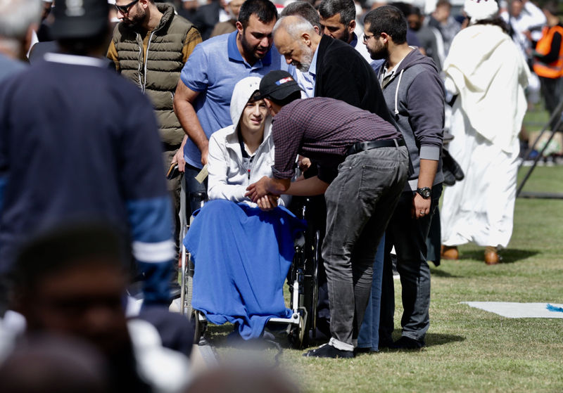Zaid Mustafa (14) greets worshippers at prayers in Hagley Park. Photo: NZ Herald