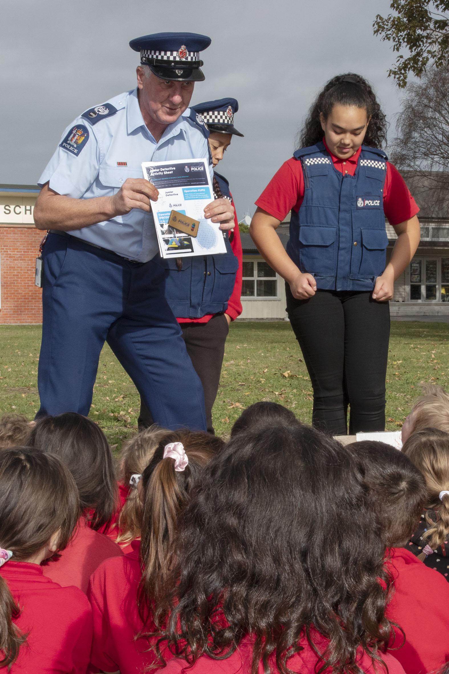 Senior Sergeant Roy Appley hands out Junior Detective activity packs. Photo: Geoff Sloan