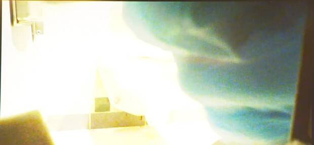 A still image taken by the covert camera showing a person wearing blue latex gloves planting the...