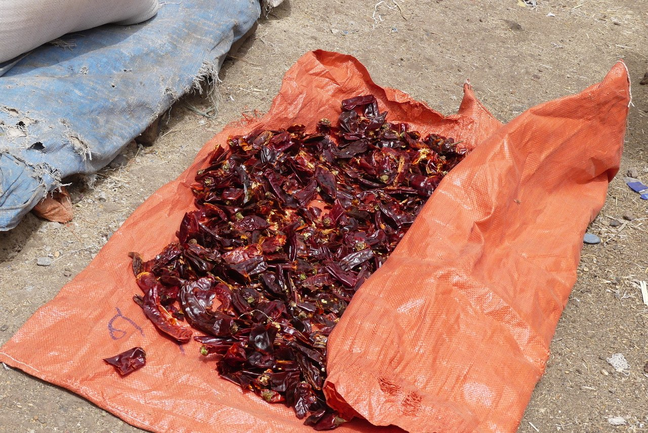 Chillies drying on the ground in a market.