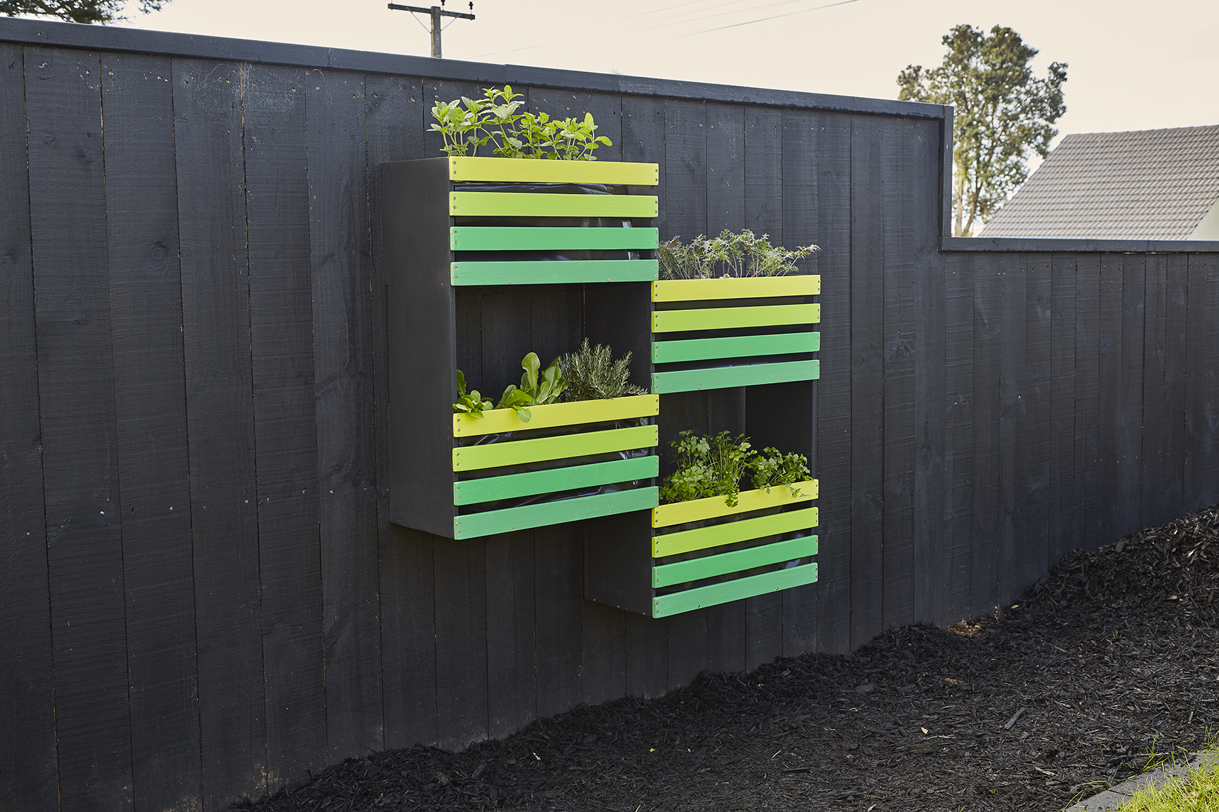 Resene All Black fence with a colourful and handy vertical garden in Resene ASAP, Resene Left...