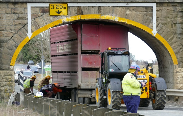 Emergency services work to dislodge the stock truck's trailer from beneath the bridge. PHOTO:...