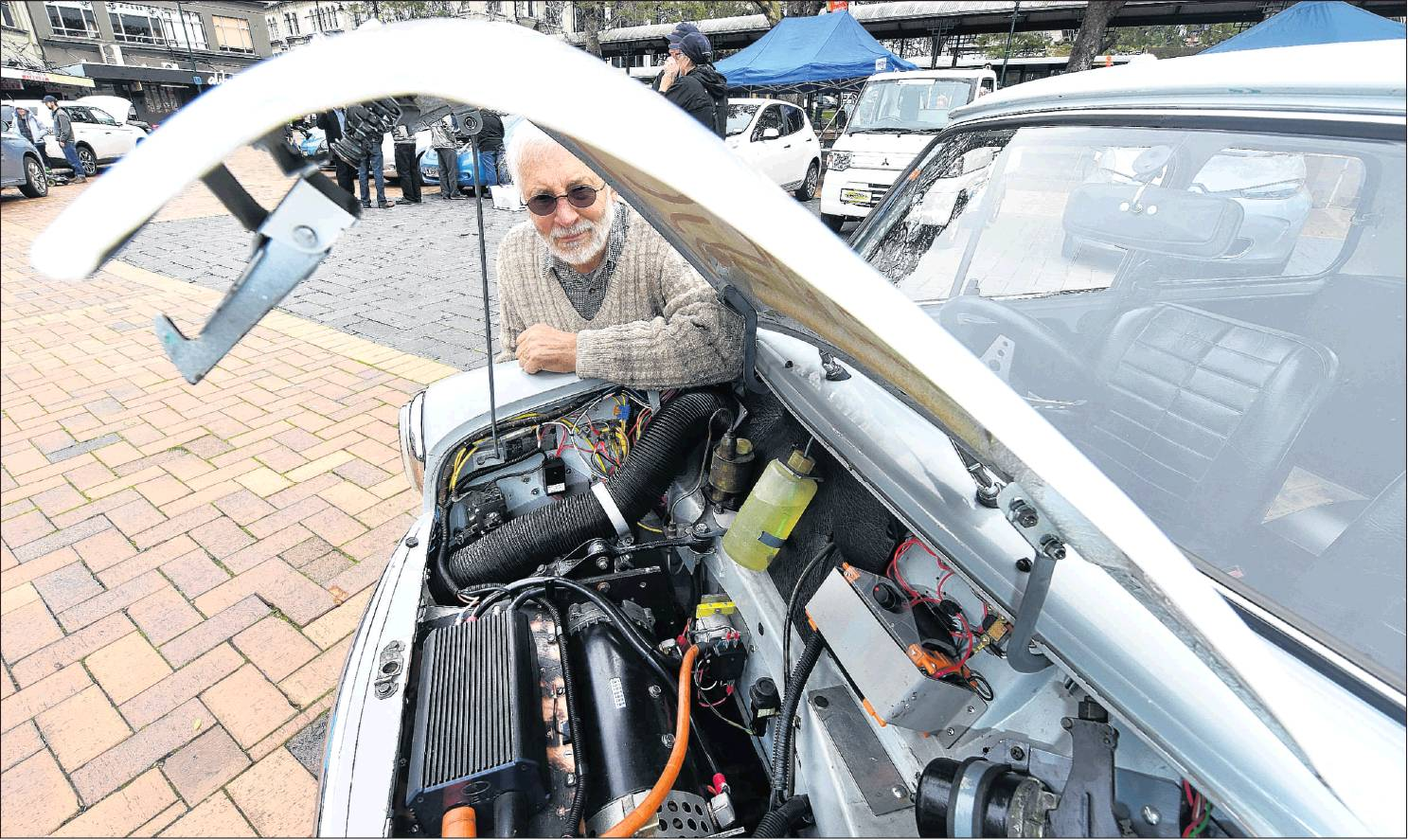 Michael Laba shows off his 1968 Morris Mini, which he converted to run on electricity in 1998, in...