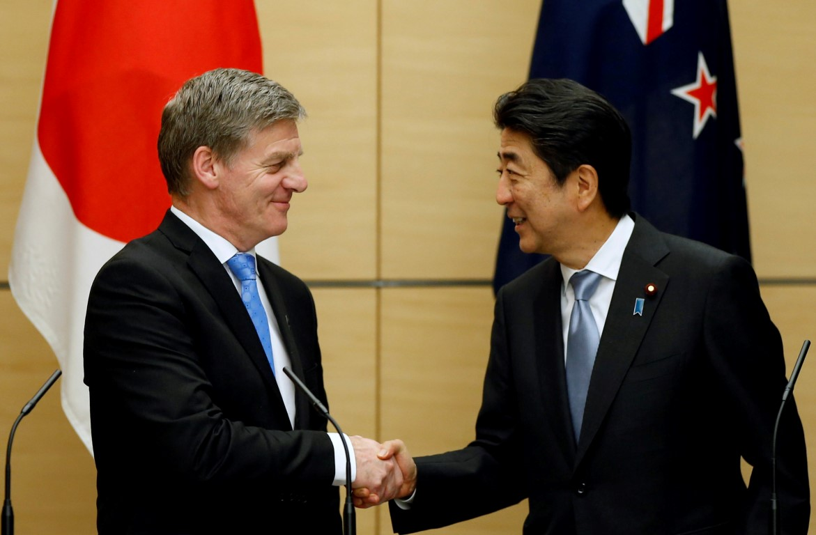 New Zealand Prime Minister Bill English (L) shakes hands with Japan's Prime Minister Shinzo Abe...
