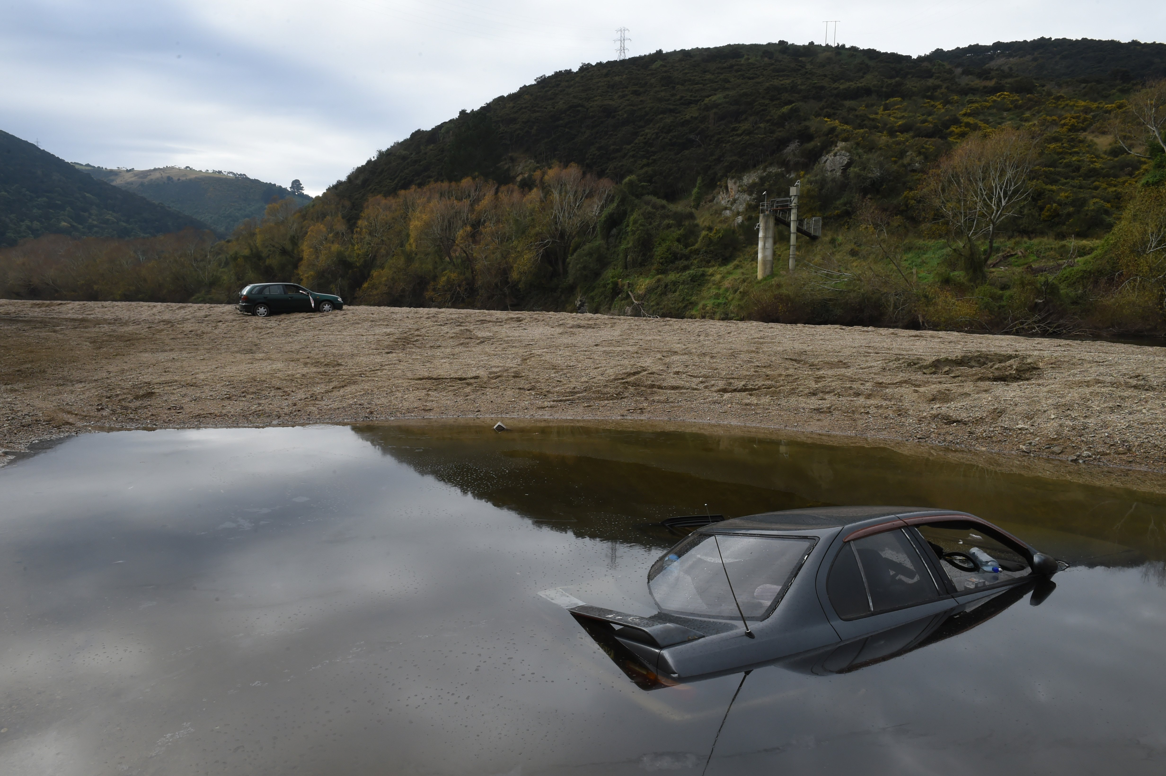 A Nissan Primera sits on the bed of the Taieri River,  and a Nissan Sentra lies abandoned at...