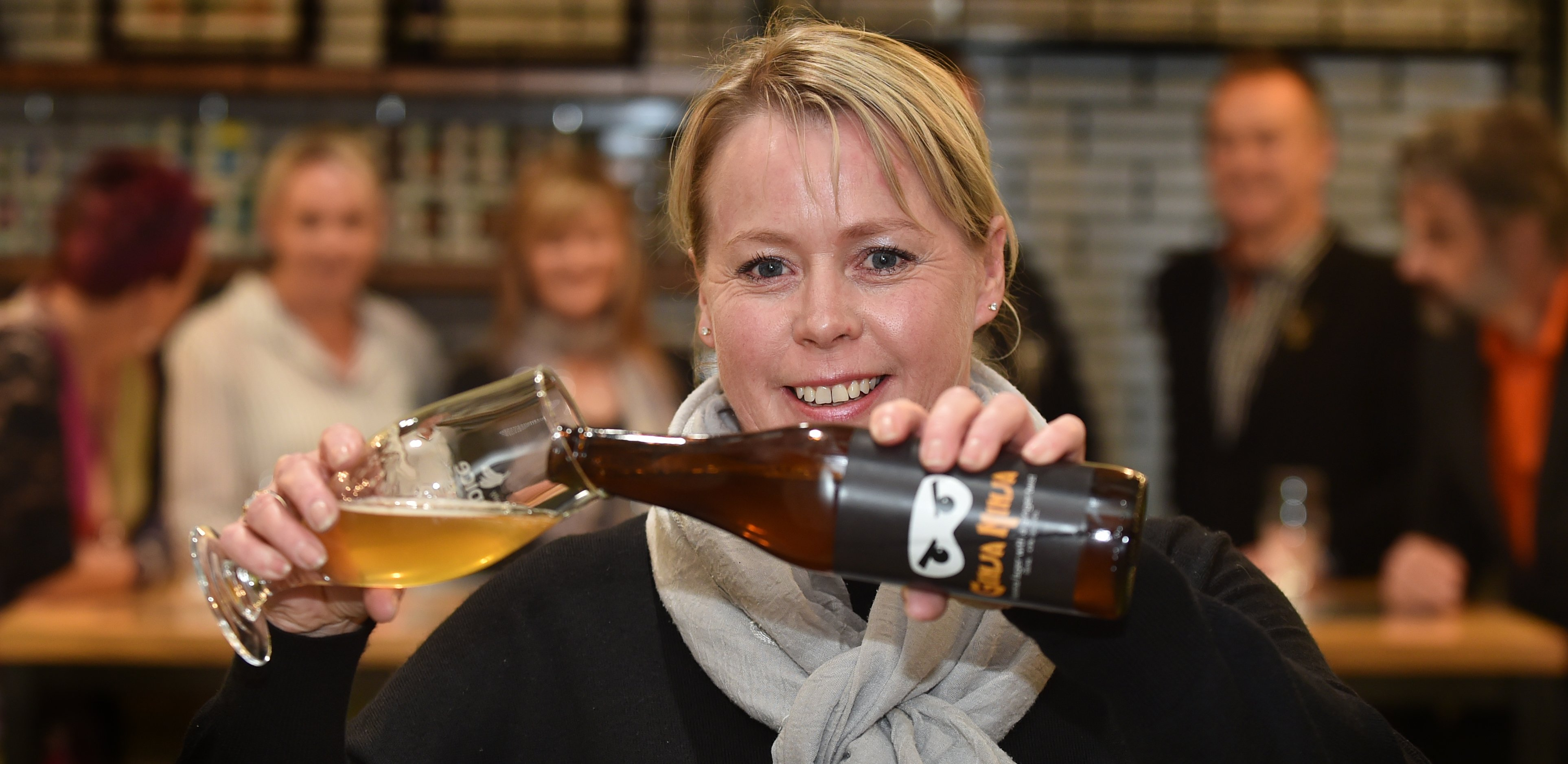 Otago Community Hospice chief executive Ginny Green pours a specially brewed ginger-infused Vienna lager at a hospice fundraising event at Otago Polytechnic on Saturday. Photo: Peter McIntosh.