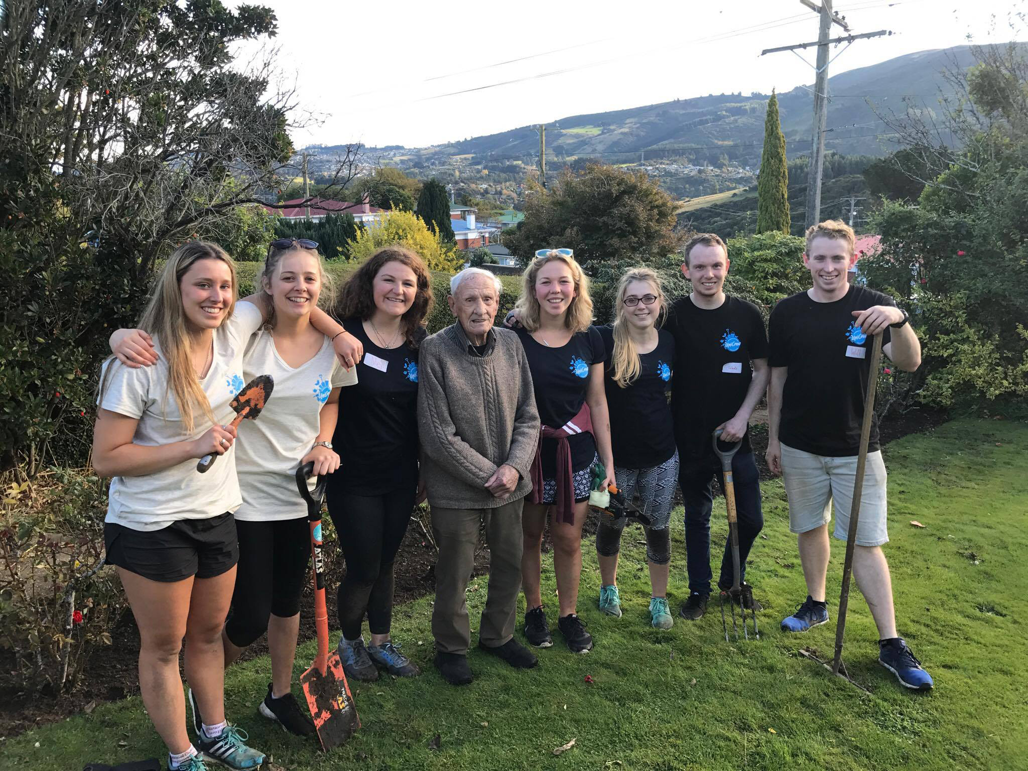 Dunedin man Vernon McArley stands in his yard with University of Otago student volunteers (from...