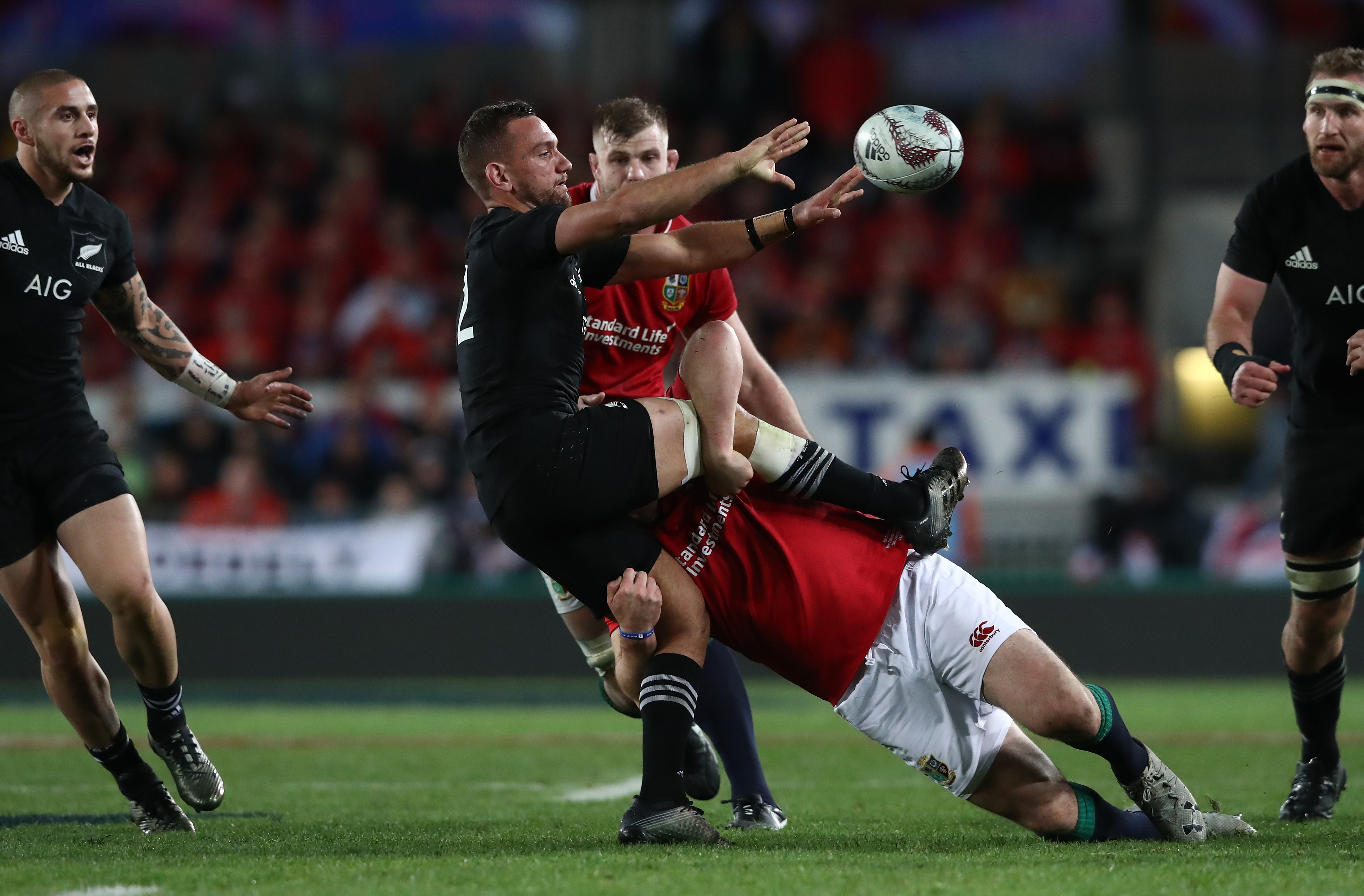 Aaron Cruden of the All Blacks offloads in the tackle. Photo: Getty