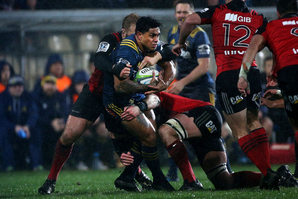Malakai Fekitoa of the Highlanders tries to break through the tackle of Owen Franks of the...
