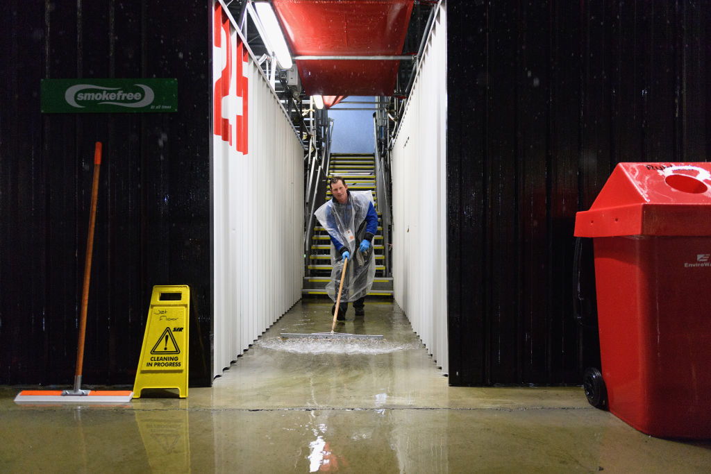 A steward works to dry the stands due to heavy rainfall prior to the Super Rugby Quarter Final...