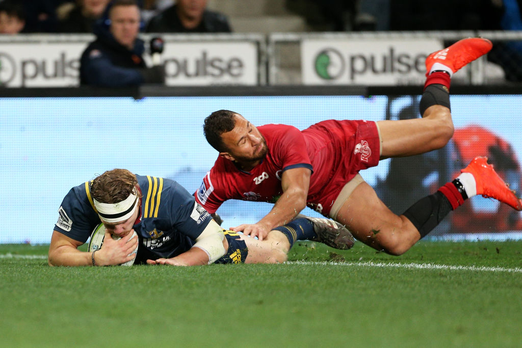 James Lentjes of the Highlanders dives over to score a try while in the tackle of Quade Cooper of...