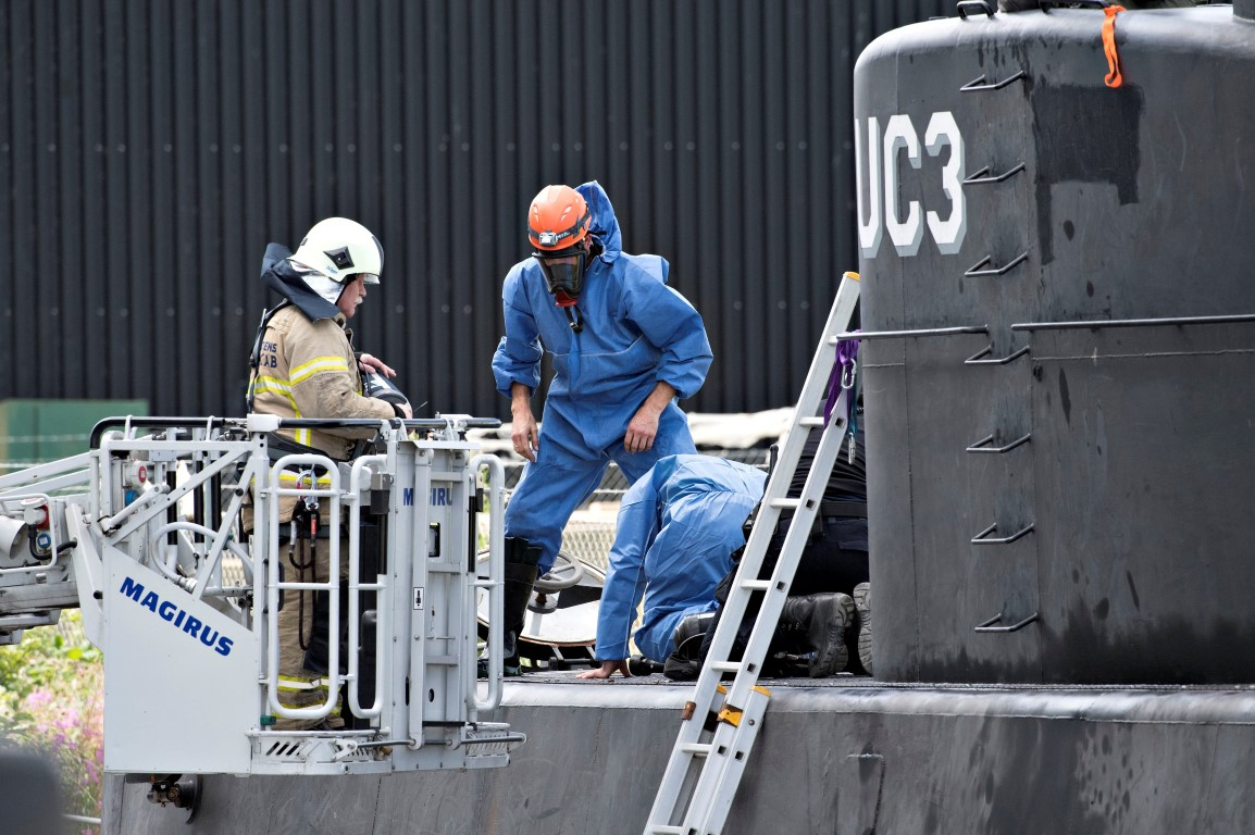 Police technicians inspect the wreck of the submarine in Copenhagen Harbour. Photo Reuters