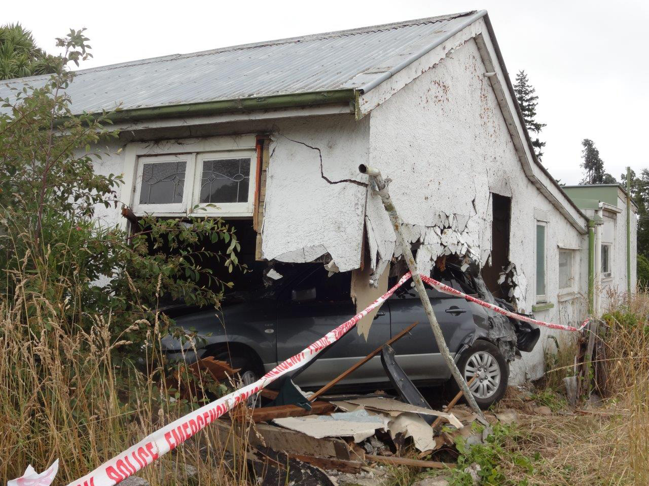 Driver flees after car crashes into house
