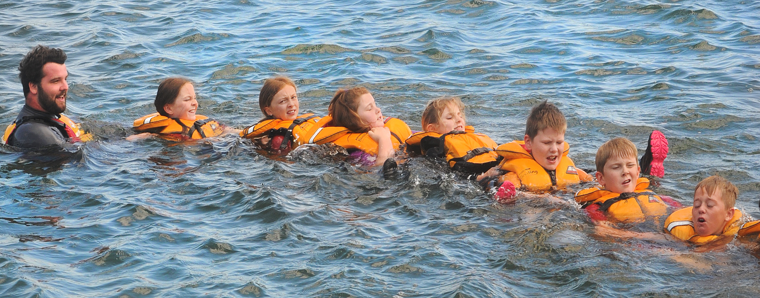 As part of their water safety programme, Swimsation instructor Ben Harrison and (from left) Imogen Harrison (10), Melanie Button (10), Grace Gemmell (9), Harmony Denston (10), James Scott (9), Ben Thompson (9) and Robbie Smith (10) form a rescue train in