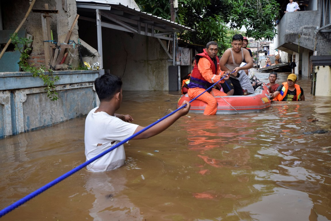 Rescue workers evacuate people from a flooded neighbourhood in Pasar Minggu, South Jakarta Photo:...
