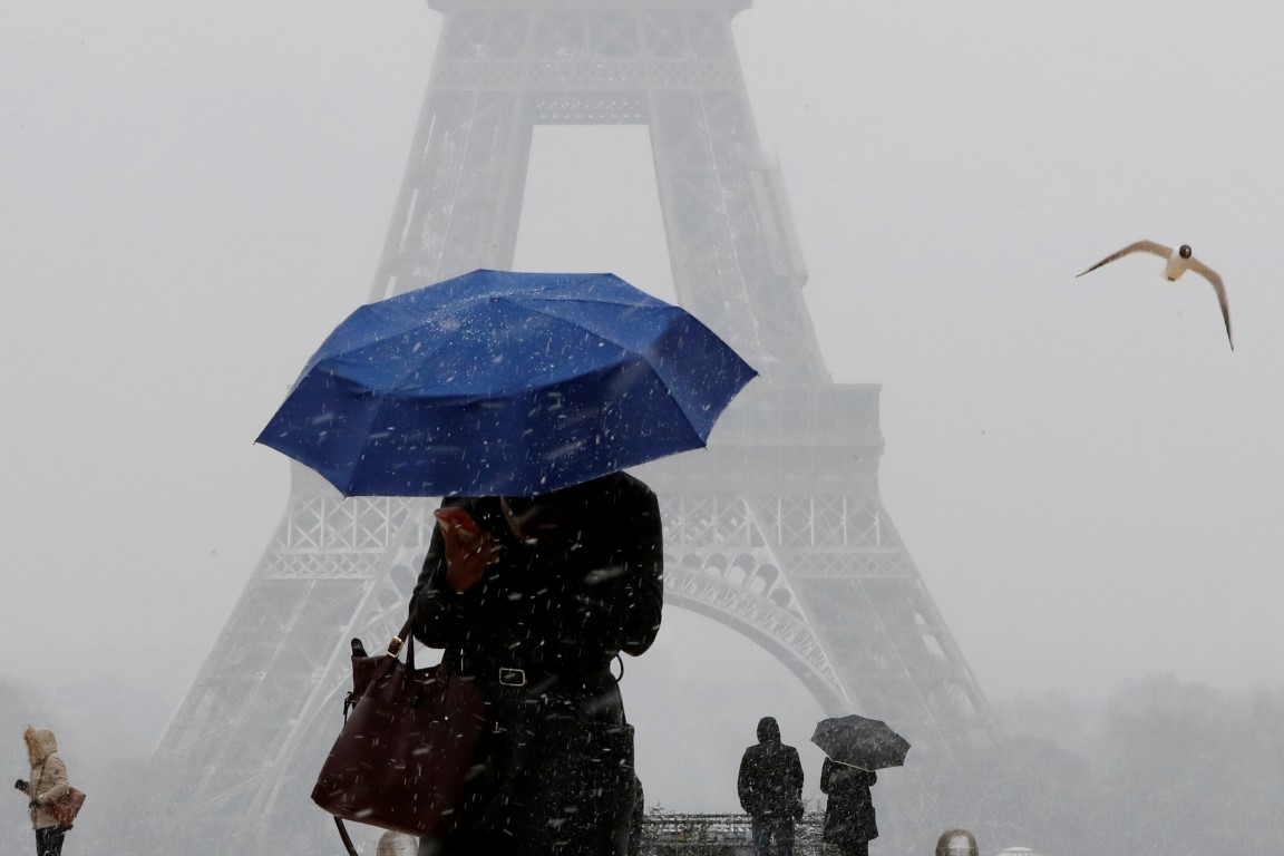 A woman uses an umbrella to protect herself from falling snow near the Eiffel Tower in Paris....