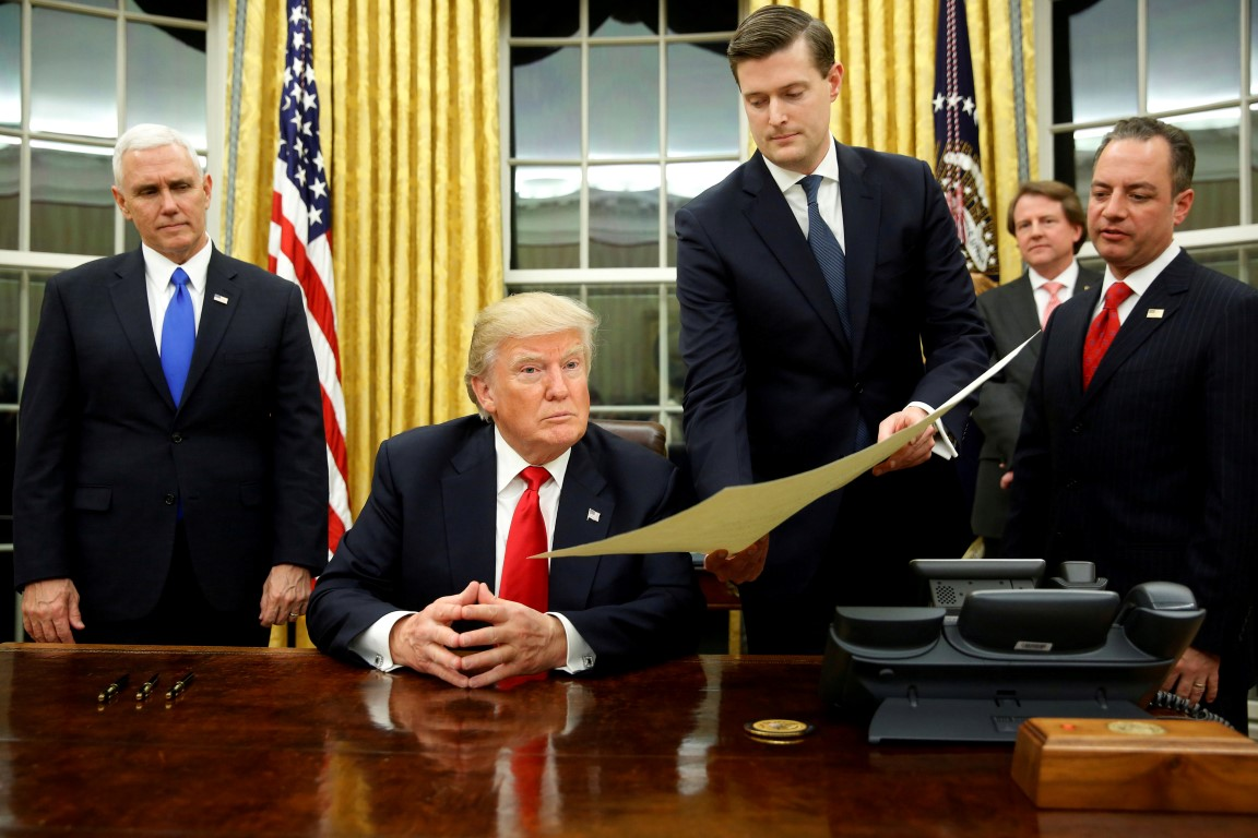 Rob Porter (then White House Staff Secretary) passes a document to President Donald Trump in the...