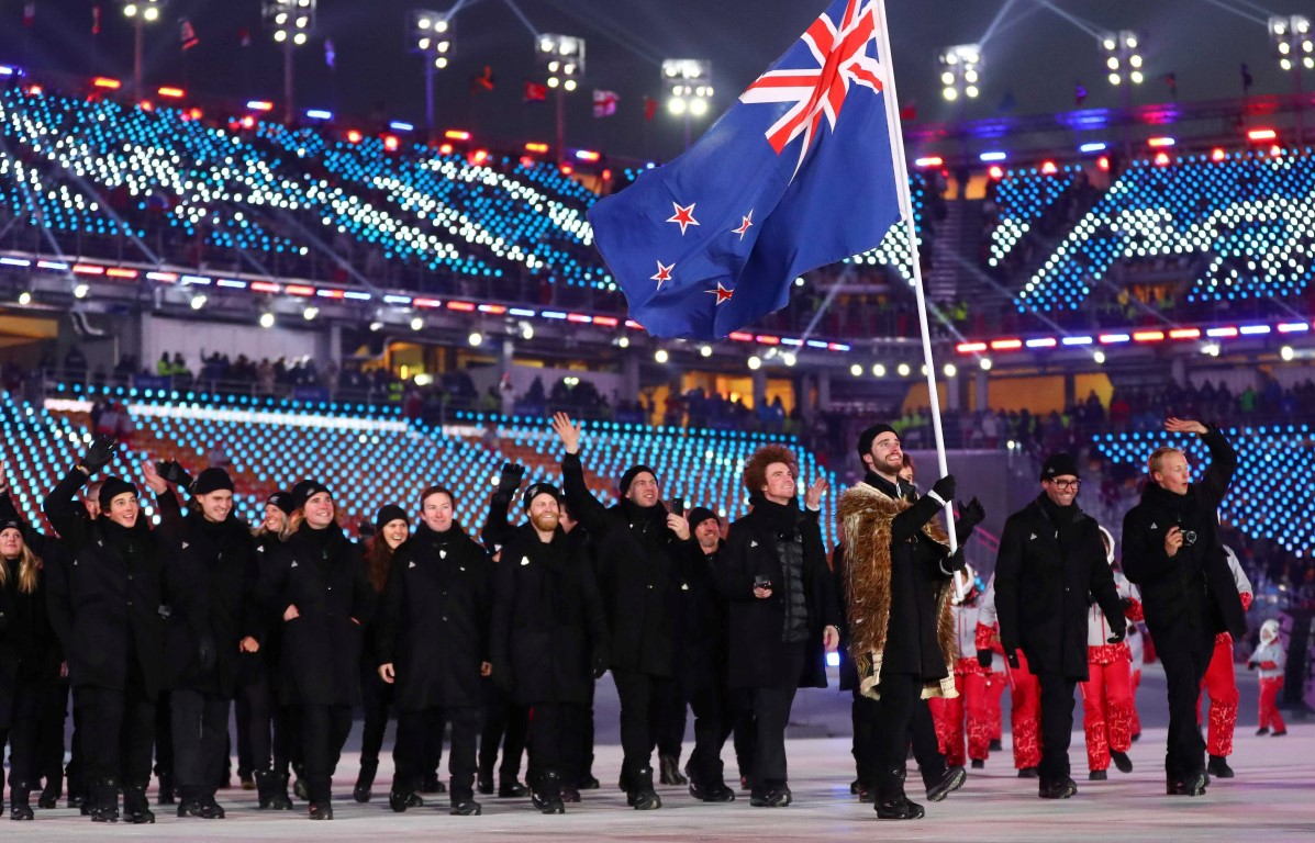 Beau-James Wells carries the national flag as he leads the New Zealand contingent during opening...