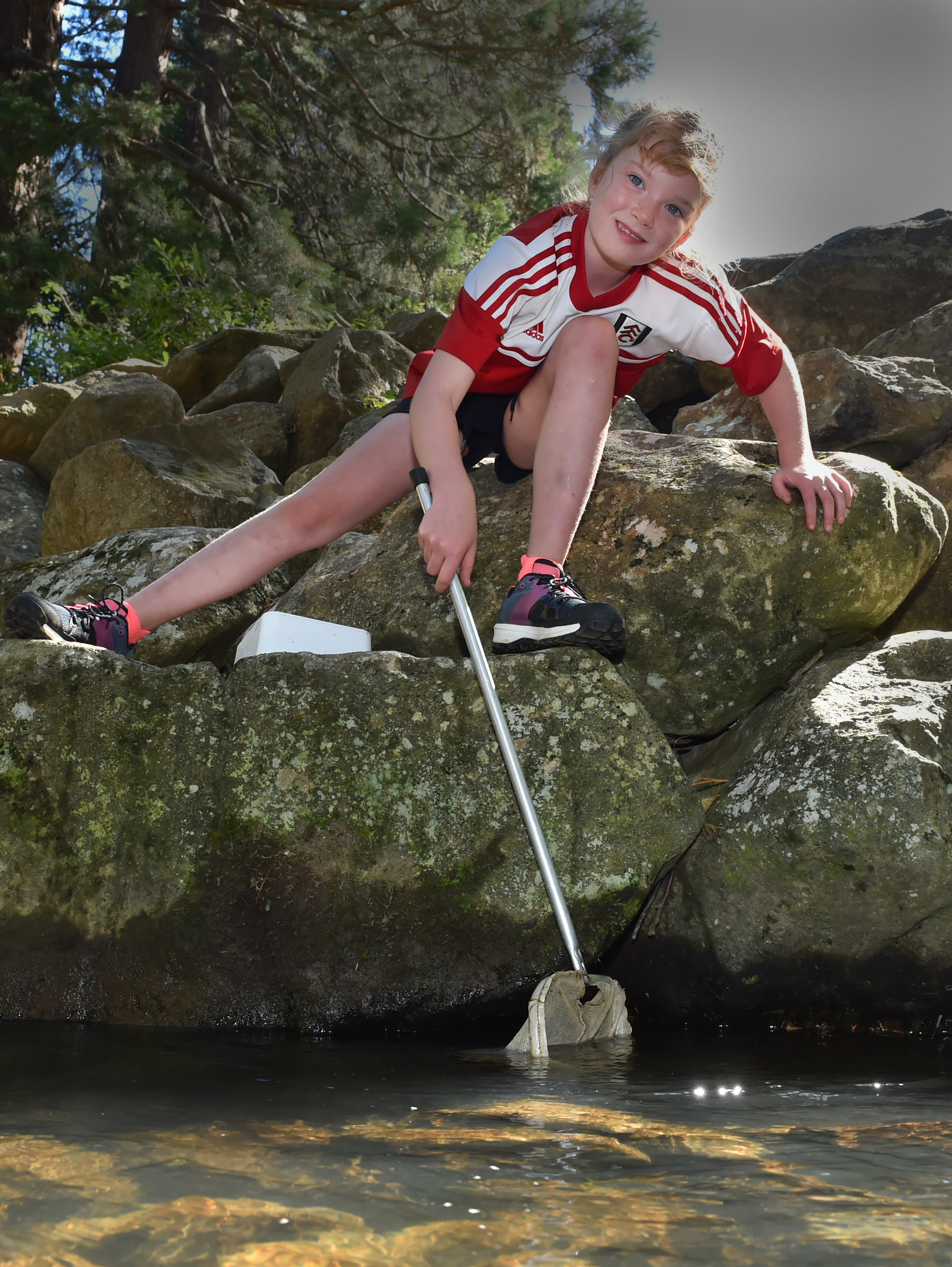 Billie Fraser (8) attempts to net creatures in Lindsay Creek as part of CreekFest in Chingford...