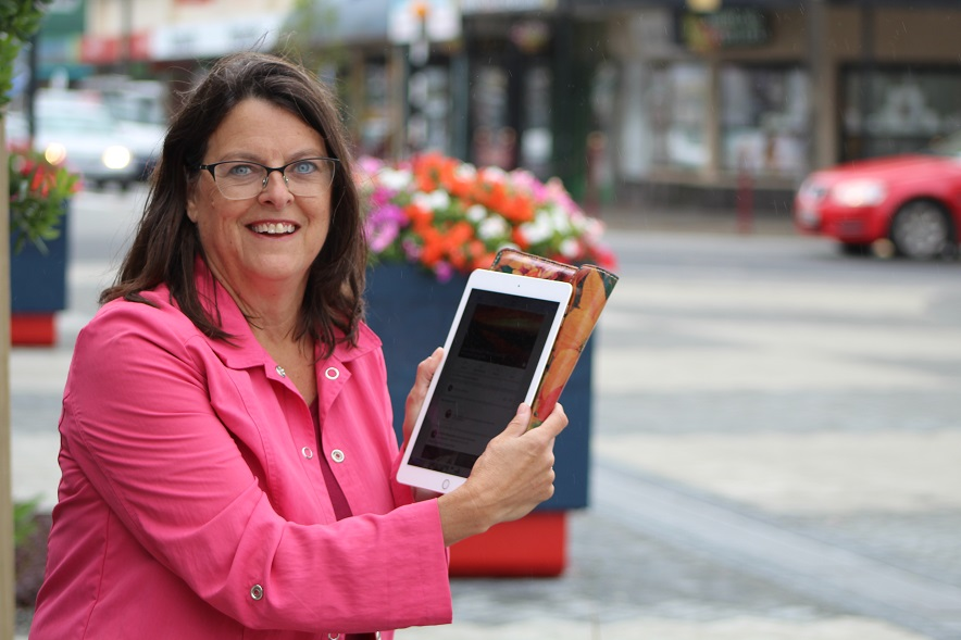 Lisa White in the Greymouth town square -- one of her favourite places -- with her iPad showing...