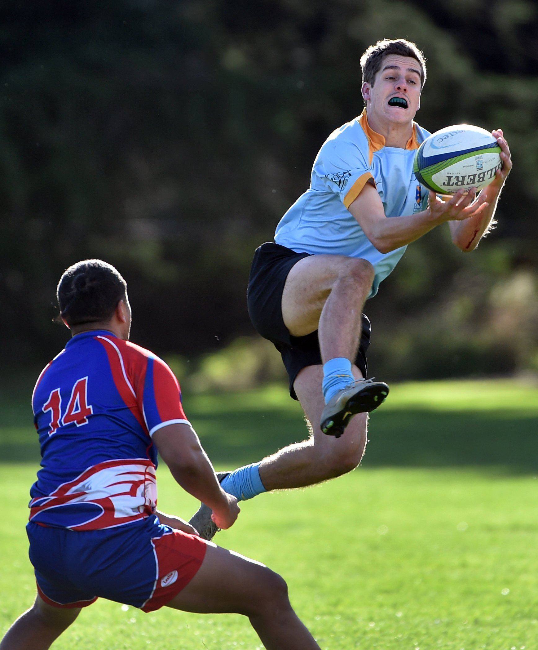 University winger Cam Gerlach catches the ball while Harbour winger Ngana Nicholas looks to...
