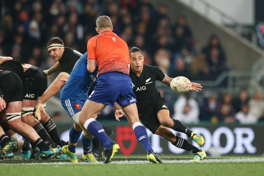 France's Baptiste Serin is blocked by referee John Lacey as All Black halfback Aaron Smith passes...
