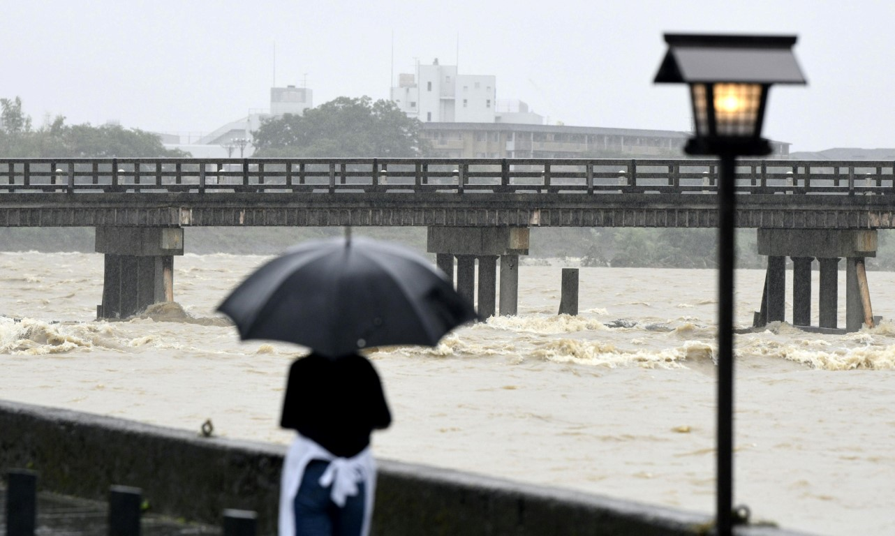 A resident watches Togetsu Bridge and the swollen Katsura River after heavy rain in Kyoto,...