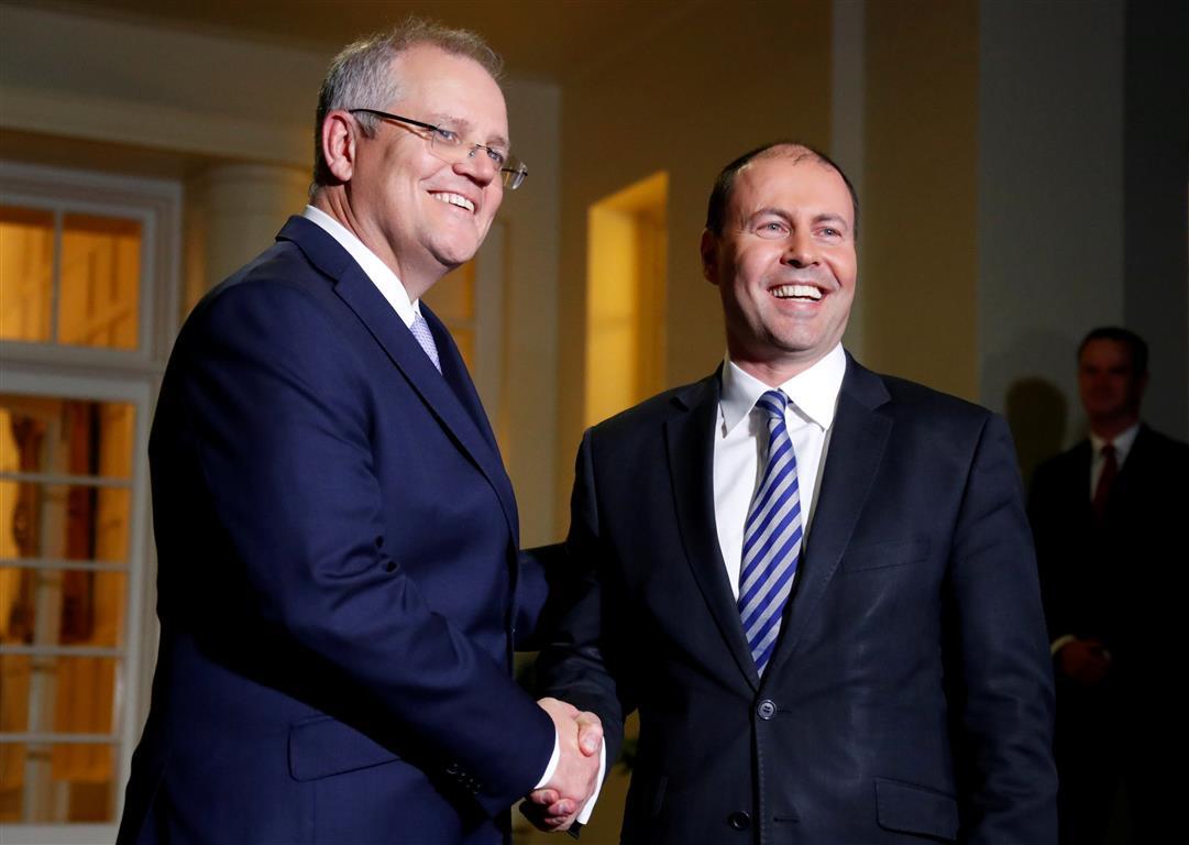 New Australian Prime Minister Scott Morrison (L) shakes hands with the new Treasurer Josh...