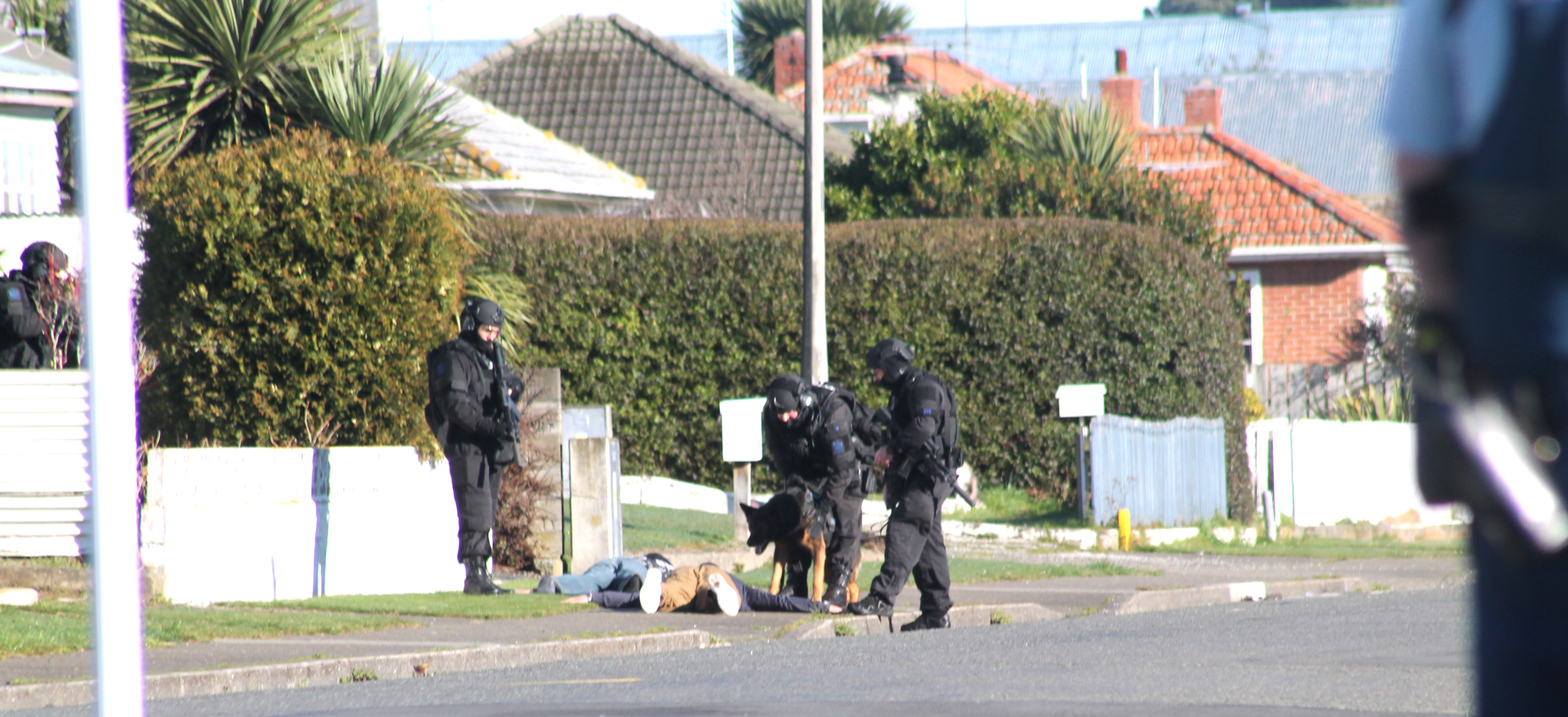 Members of the armed offenders squad deal with two men in Miller St, Invercargill on Monday, when...